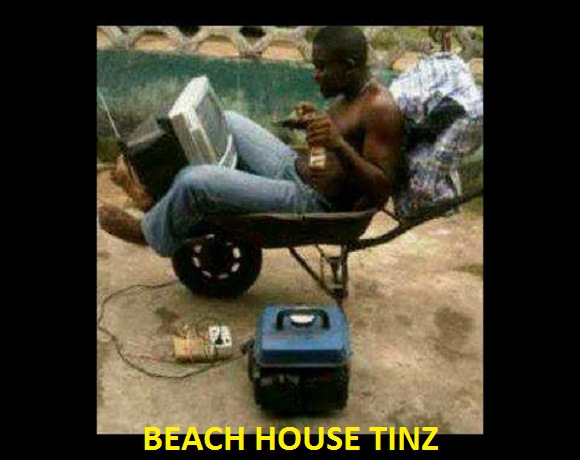 naija man sitting-in-wheel-barrow . chillin naija style